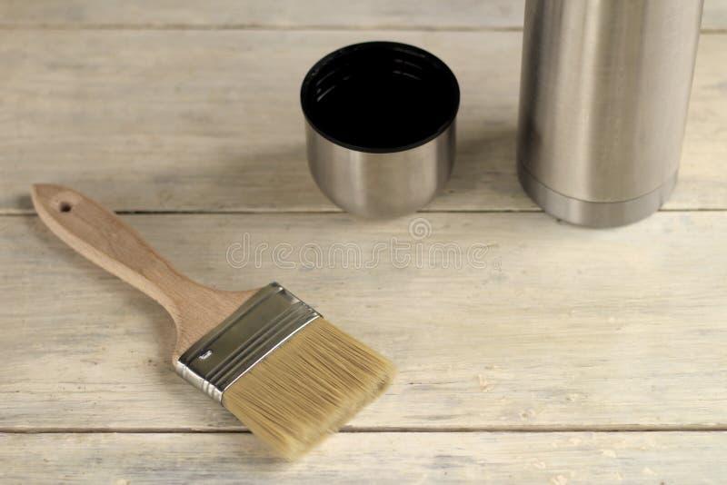 Μια βούρτσα βρίσκεται δίπλα thermos με ένα φλυτζάνι σε έναν παλαιό λευκό εκλεκτής ποιότητας ξύλινο πίνακα Θέση για το κείμενο ή τ στοκ εικόνες