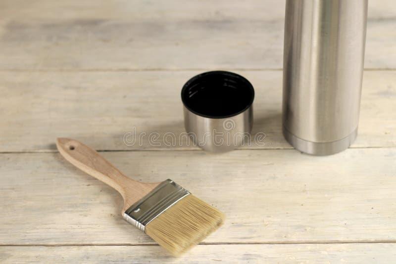 Μια βούρτσα βρίσκεται δίπλα thermos με ένα φλυτζάνι σε έναν παλαιό λευκό εκλεκτής ποιότητας ξύλινο πίνακα Θέση για το κείμενο ή τ στοκ εικόνα με δικαίωμα ελεύθερης χρήσης