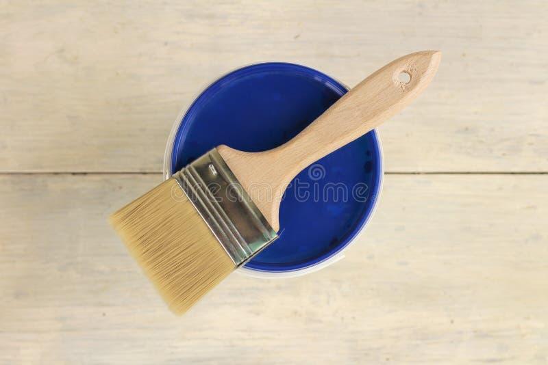 Μια βούρτσα χρωμάτων βρίσκεται στο μπλε καπάκι ενός πλαστικού κάδου χρωμάτων σε έναν παλαιό άσπρο εκλεκτής ποιότητας ξύλινο πίνακ στοκ φωτογραφία