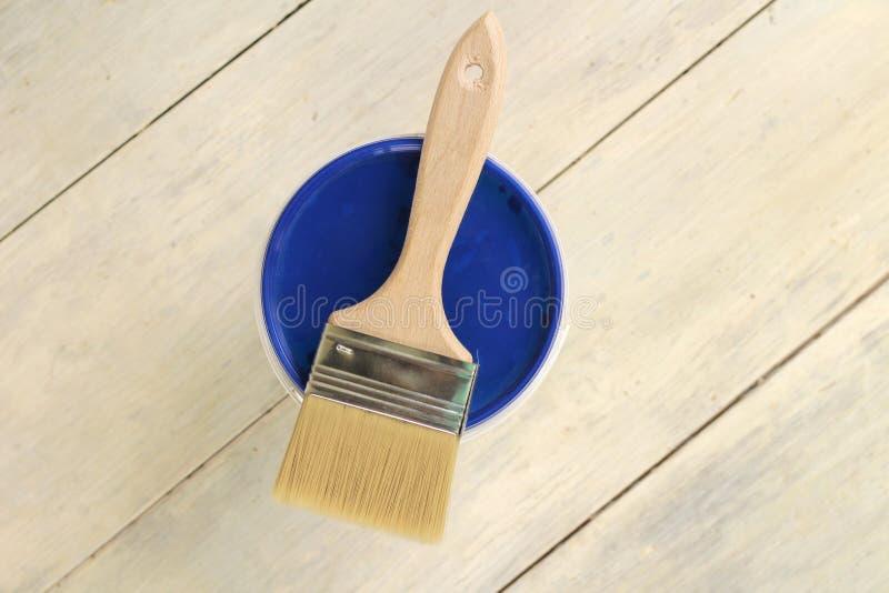Μια βούρτσα χρωμάτων βρίσκεται στο μπλε καπάκι ενός πλαστικού κάδου χρωμάτων σε έναν παλαιό άσπρο εκλεκτής ποιότητας ξύλινο πίνακ στοκ φωτογραφίες με δικαίωμα ελεύθερης χρήσης