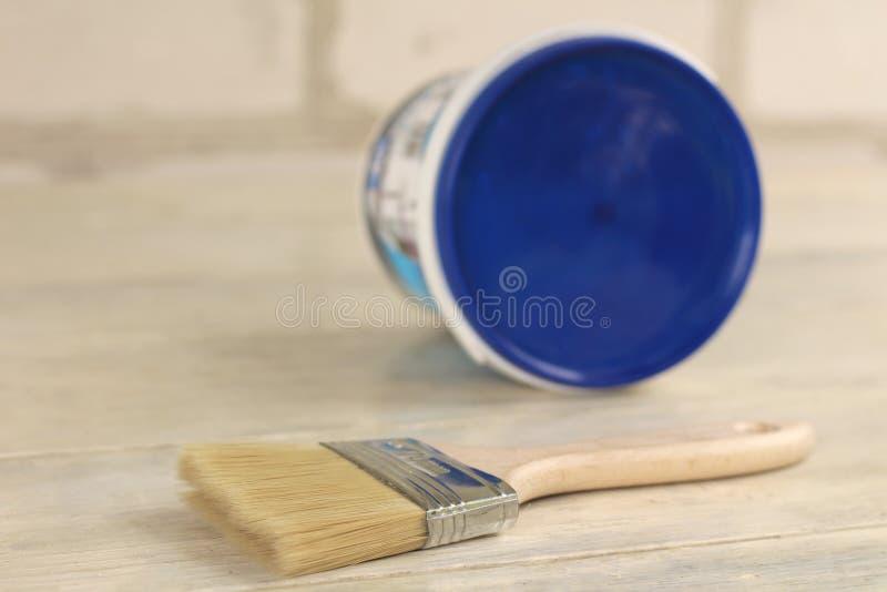 Μια βούρτσα χρωμάτων είναι δίπλα σε έναν πλαστικό κάδο χρωμάτων με ένα μπλε καπάκι σε έναν παλαιό λευκό εκλεκτής ποιότητας ξύλινο στοκ φωτογραφίες