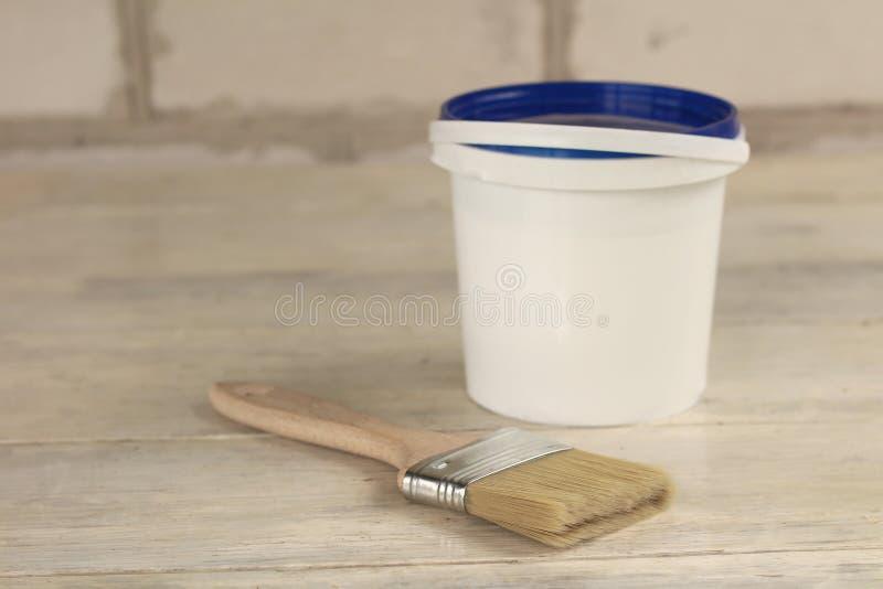 Μια βούρτσα χρωμάτων είναι δίπλα σε έναν πλαστικό κάδο χρωμάτων με ένα μπλε καπάκι σε έναν παλαιό λευκό εκλεκτής ποιότητας ξύλινο στοκ φωτογραφία με δικαίωμα ελεύθερης χρήσης