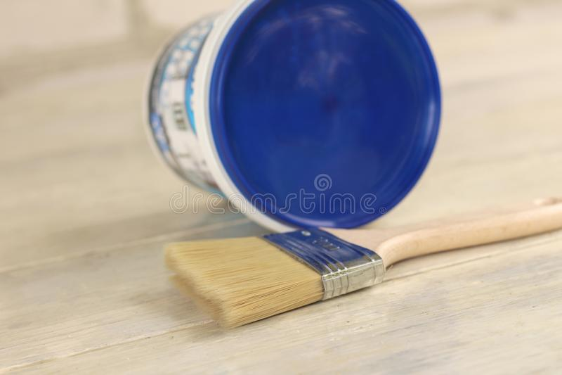 Μια βούρτσα χρωμάτων είναι δίπλα σε έναν πλαστικό κάδο χρωμάτων με ένα μπλε καπάκι σε έναν παλαιό λευκό εκλεκτής ποιότητας ξύλινο στοκ φωτογραφίες με δικαίωμα ελεύθερης χρήσης