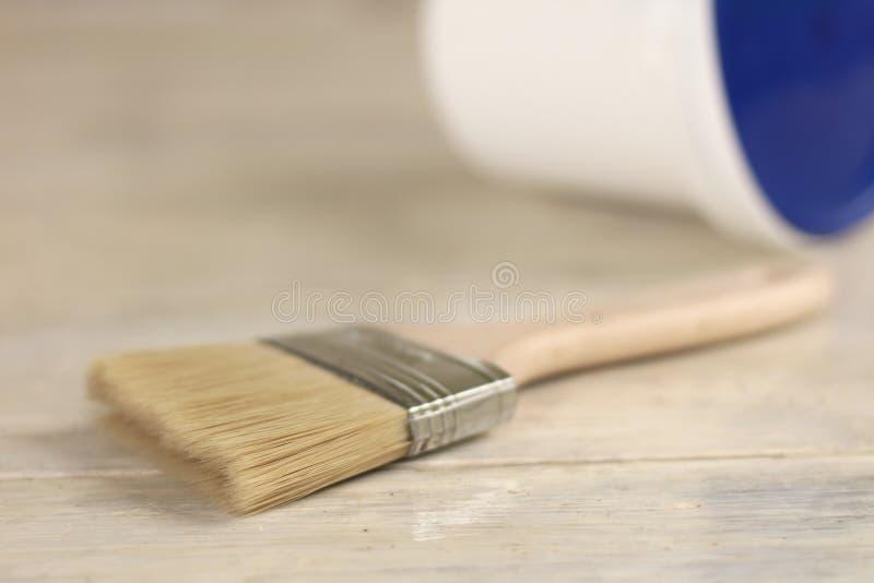 Μια βούρτσα χρωμάτων είναι δίπλα σε έναν πλαστικό κάδο χρωμάτων με ένα μπλε καπάκι σε έναν παλαιό λευκό εκλεκτής ποιότητας ξύλινο στοκ φωτογραφία