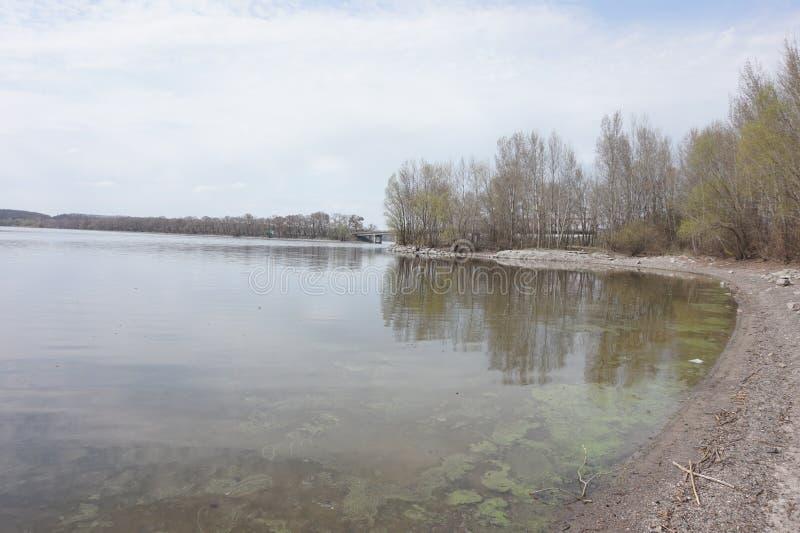 Όχθη ποταμού την πρώιμη άνοιξη Μια γέφυρα μπορεί να δει στην απόσταση E στοκ φωτογραφία με δικαίωμα ελεύθερης χρήσης
