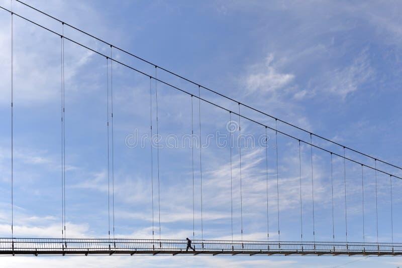 Μια γέφυρα πάνω από ένα ποτάμι με έναν άντρα να περπατά κατά μήκος του γαλάζιου ουρανού στοκ φωτογραφίες με δικαίωμα ελεύθερης χρήσης