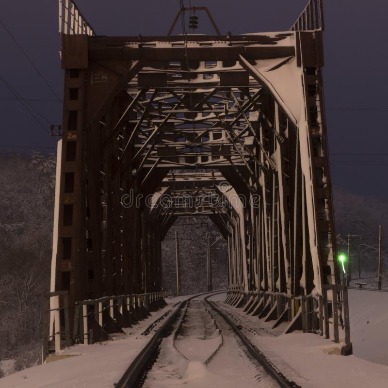 Μια γέφυρα σιδηροδρόμων στην ομίχλη ή τον καπνό πρωινού μέσω των οποίων οι ακτίνες του ήλιου λάμπουν στοκ εικόνες