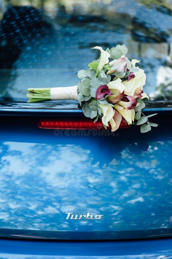 μια γαμήλια ανθοδέσμη βρίσκεται σε ένα όμορφο μπλε αυτοκίνητο Γαμήλιες διακοσμήσεις στοκ φωτογραφία με δικαίωμα ελεύθερης χρήσης