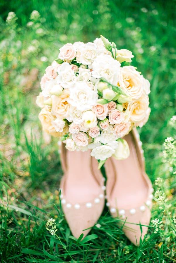 Μια γαμήλια ευγενής ανθοδέσμη των άσπρων και ρόδινων τριαντάφυλλων και των ψηλοτάκουνων παπουτσιών σε μια πράσινη χλόη μπλε garte στοκ εικόνες