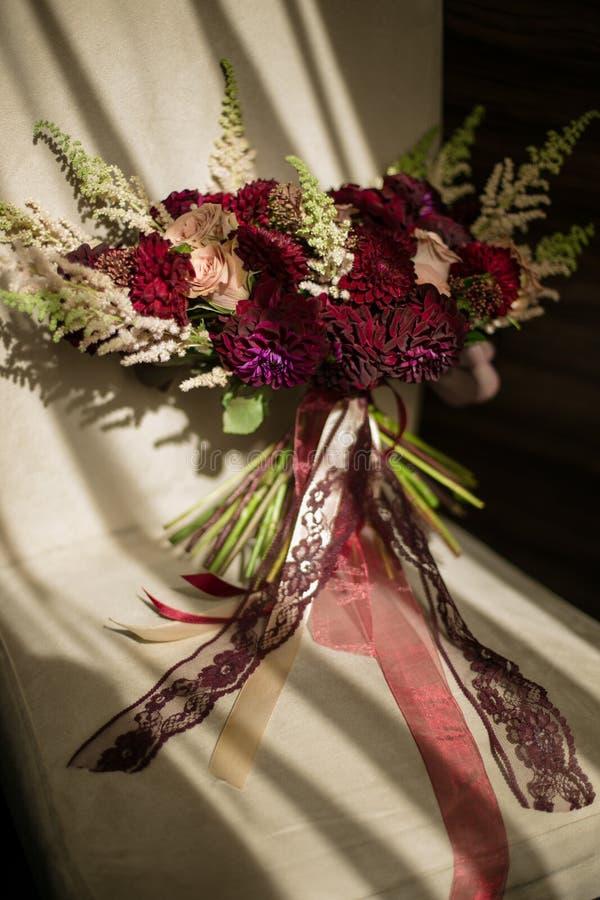 Μια γαμήλια μεγάλη ανθοδέσμη burgundy στις σκιές, που διακοσμούνται με τα πράσινα και τις κορδέλλες, στον ήλιο στοκ εικόνες