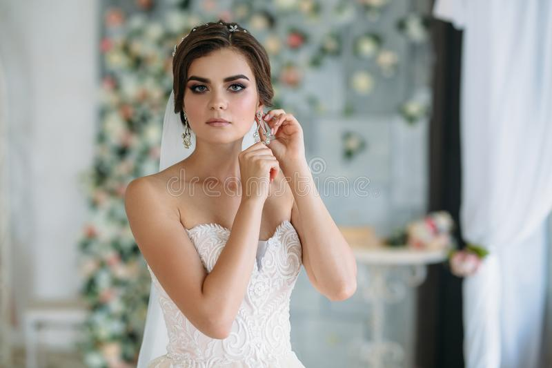 Μια γλυκιά νέα νύφη στη ημέρα γάμου πηγαίνει και βάζει στα σκουλαρίκια στο αυτί της Όμορφο κορίτσι brunette με την τρίχα και στοκ εικόνες με δικαίωμα ελεύθερης χρήσης