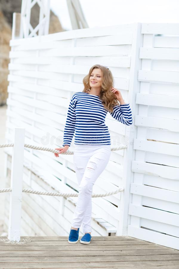 Μια γοητευτική αρκετά νέα γυναίκα hipster στη θερινή άσπρη μπλούζα στα πάνινα παπούτσια στα καθιερώνοντα τη μόδα τζιν στα μοντέρν στοκ φωτογραφία