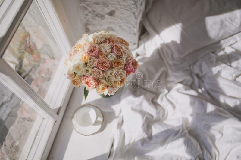 Μια γοητευτική μεγάλη ανθοδέσμη των τριαντάφυλλων και ενός άσπρου φλυτζανιού τσαγιού είναι στο windowsill δίπλα στο κρεβάτι στοκ φωτογραφία