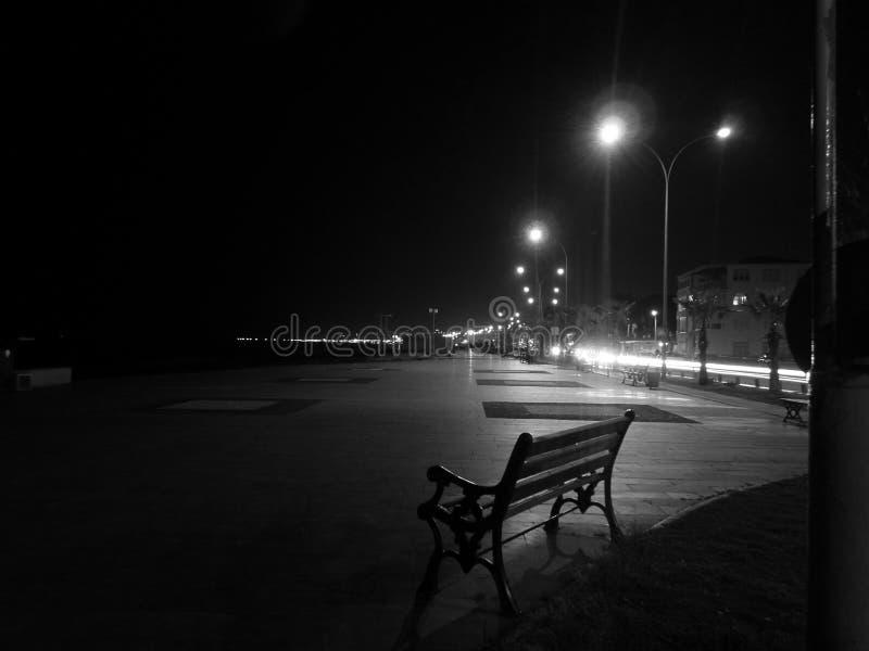 Μια γραπτή φωτογραφία μιας νύχτας, ένας κενός πάγκος στην παραλία στην περιοχή Atakum, SAMSUN, και τα φω'τα της ακτής στοκ φωτογραφίες