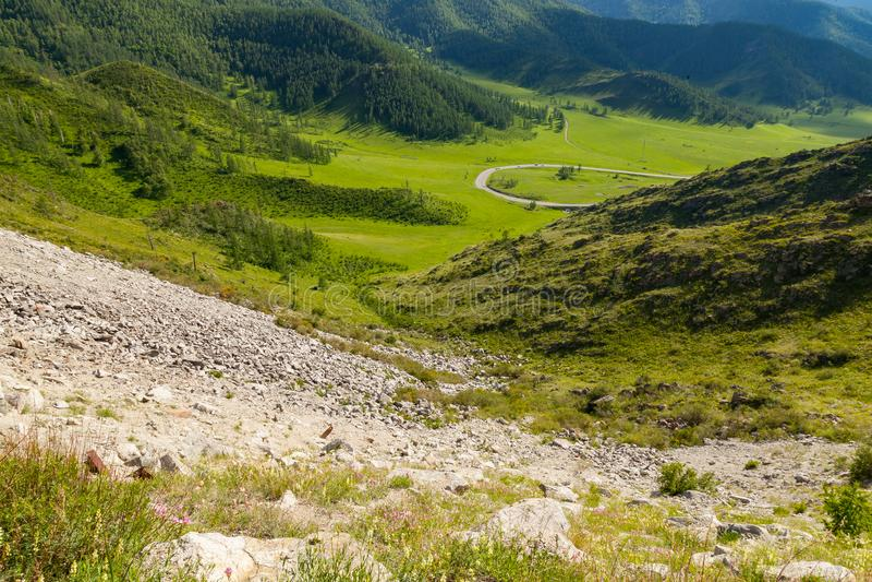 Μια γραφική θέση στα βουνά Altai με τα πράσινα δέντρα και χλόη στις άγρια περιοχές με έναν δρόμο με πολλ'ες στροφές στο πόδι κάτω στοκ φωτογραφία με δικαίωμα ελεύθερης χρήσης