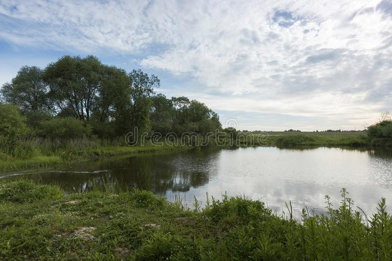 Μια γραφική λίμνη με τις πράσινα τράπεζες και τα σύννεφα στο μπλε ουρανό στοκ εικόνα