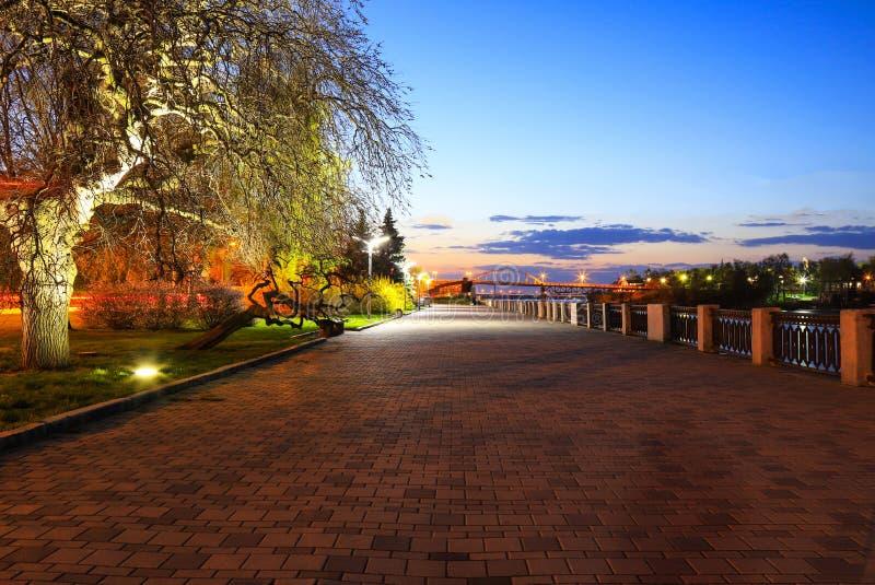 Μια γραφική οδός πετρών, μια αποβάθρα με τα καφετιά κεραμίδια, αναμμένα από τα φανάρια σε μια νύχτα άνοιξη Μεγάλο παλαιό δέντρο κ στοκ εικόνες με δικαίωμα ελεύθερης χρήσης