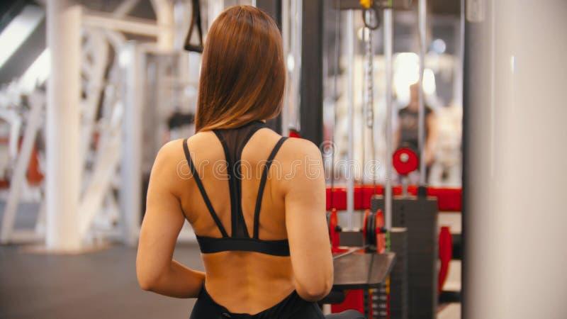 Μια γυναίκα αθλητών που ασκεί στη συνεδρίαση γυμναστικής στο trainning προσομοιωτή στοκ εικόνα με δικαίωμα ελεύθερης χρήσης