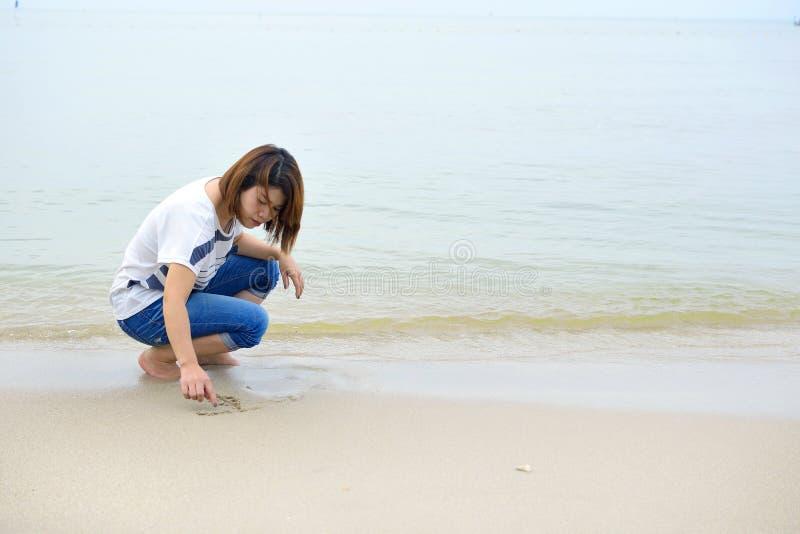 Μια γυναίκα γράφει στην παραλία άμμου στοκ φωτογραφία με δικαίωμα ελεύθερης χρήσης