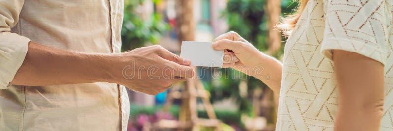 Μια γυναίκα δίνει σε ένα ανδρών μακροχρόνιο σχήμα ΕΜΒΛΗΜΑΤΩΝ καρτών ή επαγγελματικών καρτών ασφάλειας βασικό στοκ εικόνες