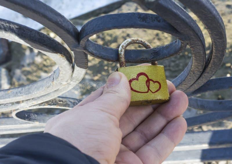 Μια γυναίκα ελέγχει τη γαμήλια κλειδαριά της, που κρεμιέται τρία πριν από χρόνια στοκ εικόνα