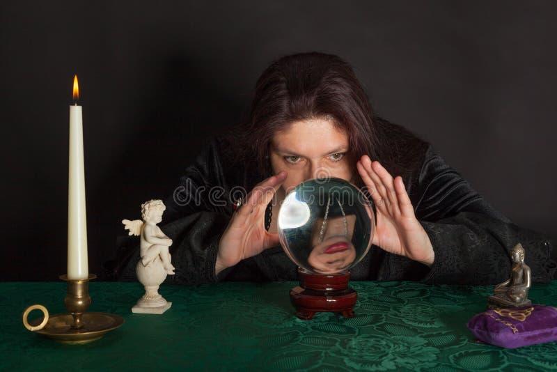 Μια γυναίκα εξετάζει μια σφαίρα κρυστάλλου στοκ φωτογραφία