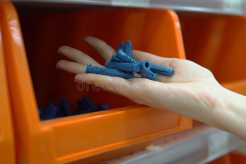 Μια γυναίκα επιλέγει τα ζαρωμένα πλαστικά βουλώματα σε ένα κατάστημα των αγαθών κατασκευής στοκ εικόνες