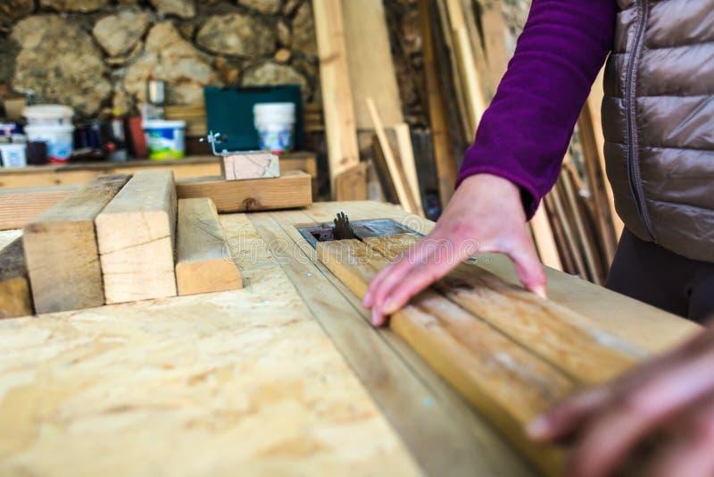 Μια γυναίκα εργάζεται σε ένα εργαστήριο ξυλουργικής στοκ εικόνες