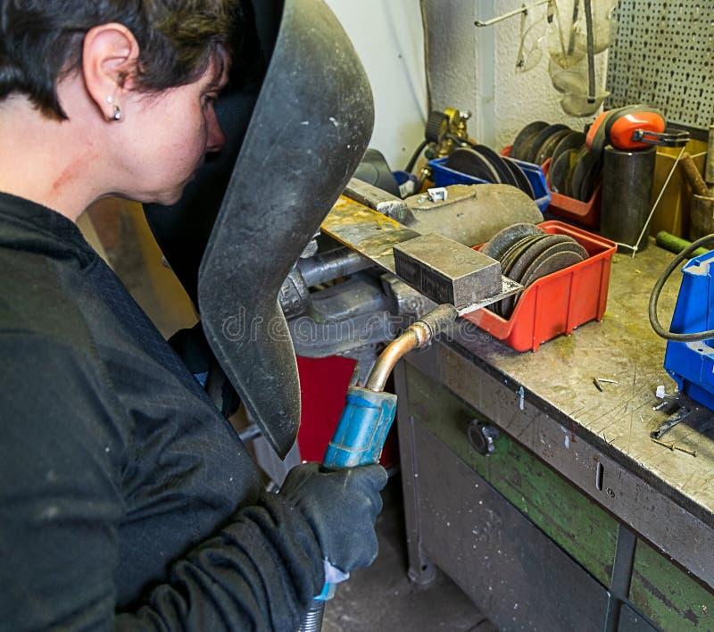 Μια γυναίκα θέλει να ενώσει στενά μαζί δύο κομμάτια του μετάλλου με μια μηχανή συγκόλλησης στοκ εικόνα