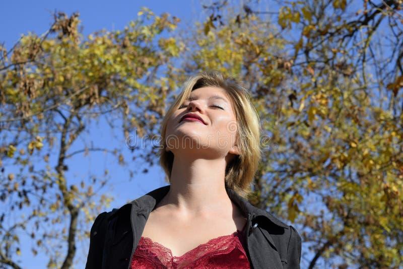 Μια γυναίκα θέτει μπροστά από μια κάμερα σε ένα πάρκο φθινοπώρου Βλαστός φωτογραφιών φθινοπώρου Φθινόπωρο στο πάρκο στοκ εικόνες