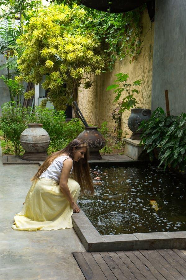 Μια γυναίκα θαυμάζει τα ψάρια σε μια λίμνη στοκ εικόνες