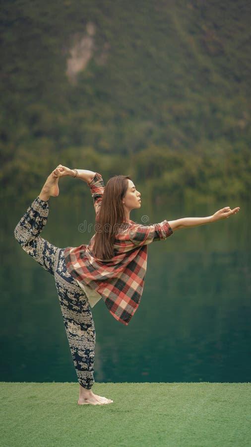 Μια γυναίκα κάνει τη γιόγκα πέρα από τη λίμνη στοκ εικόνα