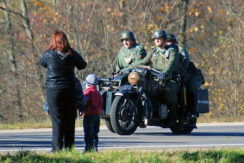 Μια γυναίκα και τα παιδιά εξετάζουν τρεις στρατιωτικούς αναδρομικό σε ομοιόμορφο στοκ φωτογραφίες