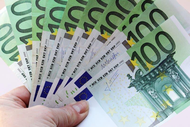 Μια γυναίκα κρατά πολλές 100 ευρο- σημειώσεις στο χέρι της στοκ εικόνα