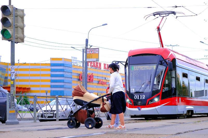 Μια γυναίκα με έναν περιπατητή στη διάβαση πεζών Τραμ πόλεων Τραμ στη μεταφορά μετρό στη Αγία Πετρούπολη r 06 12 2019 στοκ εικόνα