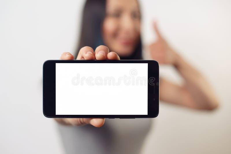 Μια γυναίκα νέων κοριτσιών κρατά ένα smartphone με την κενή άσπρη οθόνη οριζόντια μπροστά από την και χαμογελά στοκ φωτογραφίες με δικαίωμα ελεύθερης χρήσης