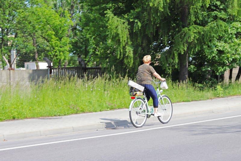 Μια γυναίκα οδηγά ένα ποδήλατο στην πλευρά της εθνικής οδού σε ένα κλίμα των πράσινων δέντρων μια ηλιόλουστη, σαφή ημέρα Εναλλακτ στοκ εικόνα με δικαίωμα ελεύθερης χρήσης