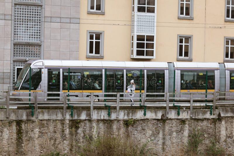 Μια γυναίκα περπατά παράλληλα με τις διαδρομές επίγειων μετρό πόλεων ` s με τα γκράφιτι στο υπόβαθρο στοκ φωτογραφία