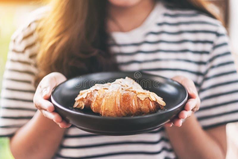Μια γυναίκα που κρατά ένα πιάτο του φρέσκου αμυγδάλου croissant στοκ εικόνες