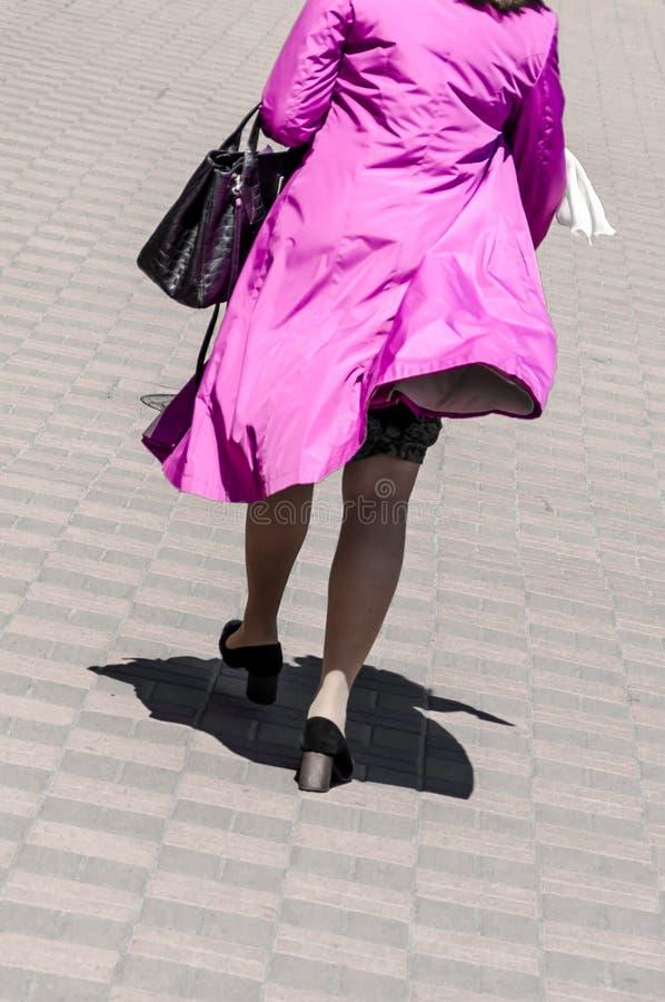 Μια γυναίκα που περπατά κατά μήκος μιας οδού πόλεων σε ένα φωτεινό ρόδινο αδιάβροχο που κυματίζει στον αέρα Άποψη από την πλάτη Χ στοκ φωτογραφία με δικαίωμα ελεύθερης χρήσης