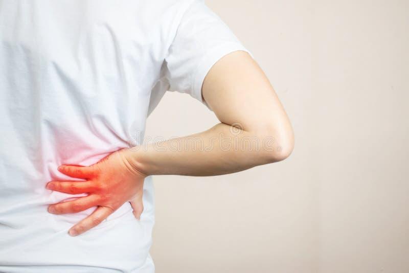 Μια γυναίκα που φορά ένα άσπρο πουκάμισο αισθάνεται έναν πόνο στην πλάτη στη δεξιά πλευρά της στοκ φωτογραφία με δικαίωμα ελεύθερης χρήσης