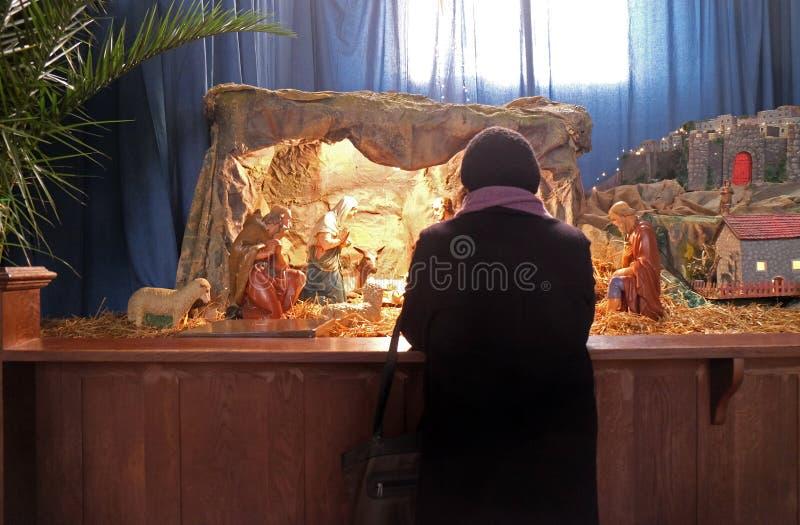 Μια γυναίκα προσεύχεται μπροστά από τους βρεφικούς σταθμούς Χριστουγέννων στη βασιλική της ιερής καρδιάς στο Ζάγκρεμπ στοκ εικόνα