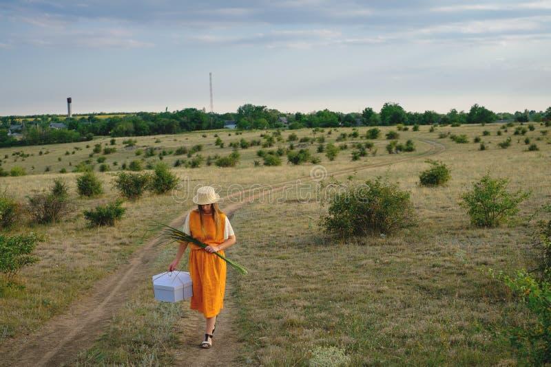 Μια γυναίκα σε ένα καπέλο αχύρου και ένα κιβώτιο δώρων περπατά στοκ φωτογραφία με δικαίωμα ελεύθερης χρήσης