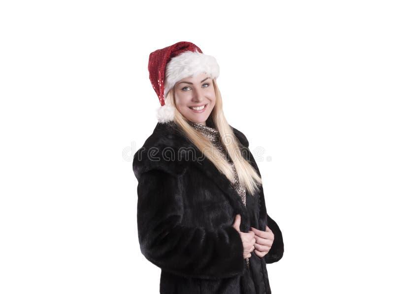 Μια γυναίκα σε ένα παλτό γουνών, που φορά ένα χαμόγελο καπέλων Άγιου Βασίλη στοκ εικόνα με δικαίωμα ελεύθερης χρήσης