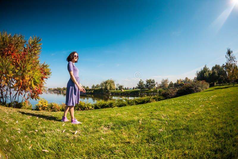 Μια γυναίκα σε ένα φόρεμα περπατά στη χλόη στοκ εικόνες