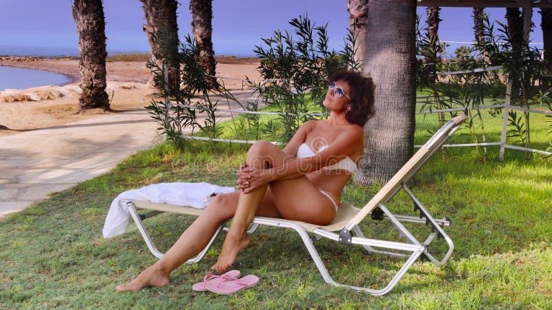 Μια γυναίκα σε μια καρέκλα σαλονιών στοκ φωτογραφίες