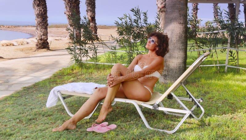 Μια γυναίκα σε μια καρέκλα σαλονιών στοκ εικόνες