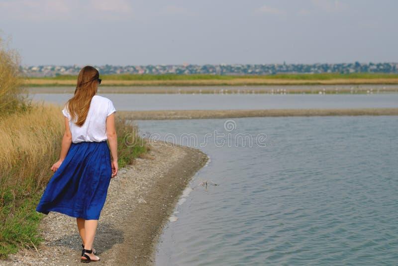 Μια γυναίκα σε μια μπλε φούστα που περπατά κατά μήκος του ποταμού στοκ φωτογραφία με δικαίωμα ελεύθερης χρήσης