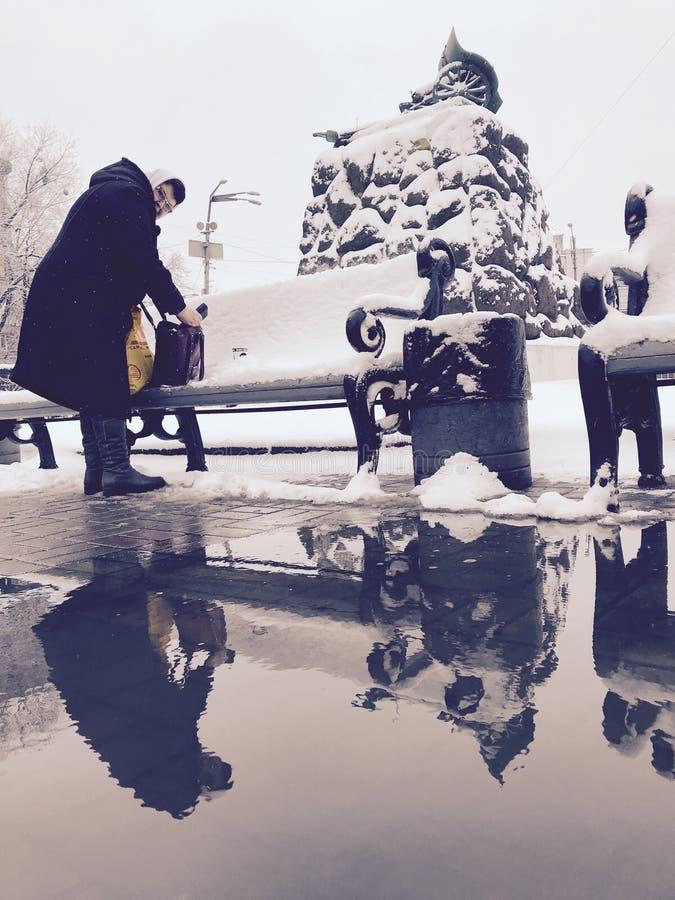 Μια γυναίκα στέκεται μπροστά από ένα χιονώδες μνημείο μπροστά από το σταθμό μετρό οπλοστασίων - Kyiv - Ουκρανία στοκ φωτογραφία
