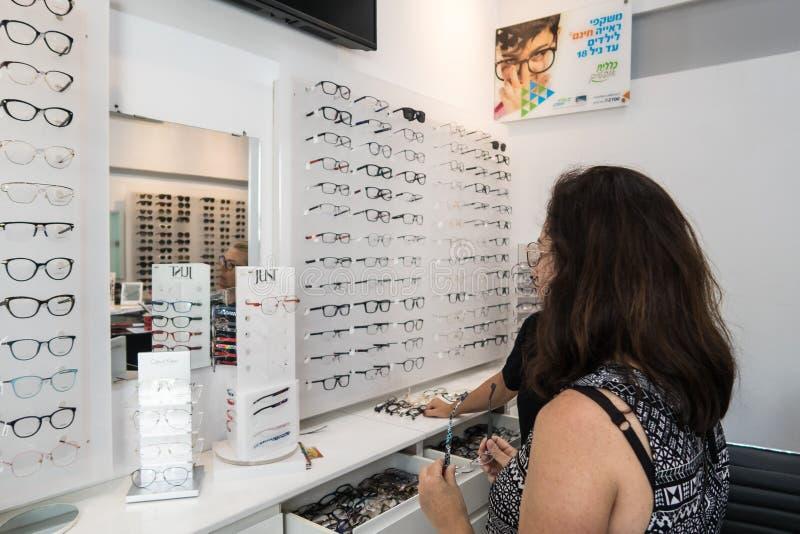 Μια γυναίκα στέκεται μπροστά από μια στάση με τα παραδείγματα των γυαλιών και επιλέγει τα γυαλιά για την ανάγνωση σε ένα οπτομετρ στοκ εικόνες